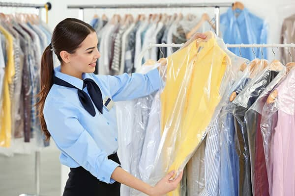 Female worker in dry-cleaning salon